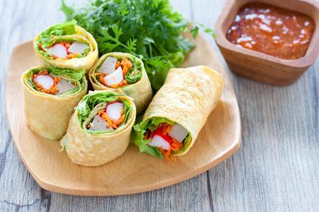 vegetarian food: Vegetarian food,Homemade egg rolls and Sweet chili sauce on wood table Stock Photo