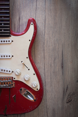 stratocaster: Red old electric guitar on old wood background
