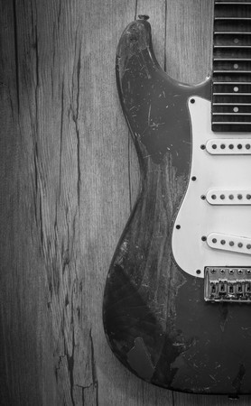 stratocaster: Old electric guitar on old wood background : Black and White Stock Photo