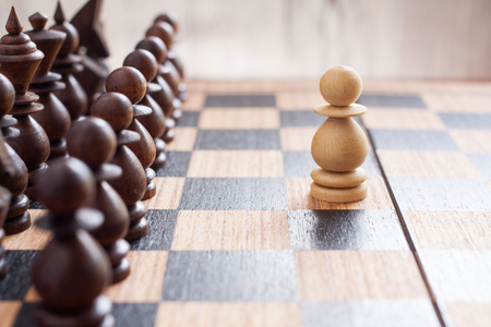 pawns: One pawn staying against all enemy team on board. Business concept . Stock Photo