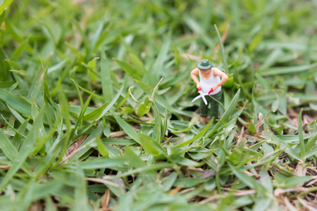 Close up of Miniature figure Senior gardener in garden cutting grass with scissors. Фото со стока - 123026354