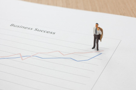 Miniature figure Businessman standing on the report graph  of  business direction strategy and success concept Banco de Imagens - 123026306