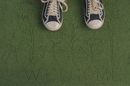 welcome mat: Black sneakers on a green welcome mat