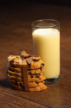 Glass of milk with raisin cookies on the table photo