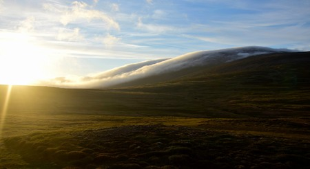 A midsummer night in Iceland. Clouds are floating down a mountain. Contre-jour. Stockfoto