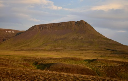 A midsummer night in Iceland. A mountain is glowing in the midnight sun. The Vatnsdalsfjall near Blönduos. A light blue sky.