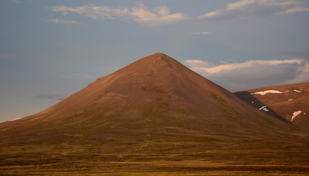 A midsummer night in Iceland. A mountain is glowing in the midnight sun. The Svinadalsfjall near Blönduos. A light blue sky.