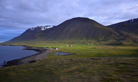 Icelandic landscape with the campsite at the hot pot Grettislaug on peninsula Skagi.A few buildings and in the background a mountain in the evening sun.