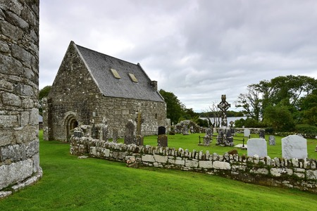The ruins of an ancient church and a cemetery on Holy Island in Lough Derg in Ireland, County Clare. On the left a part of a round tower.