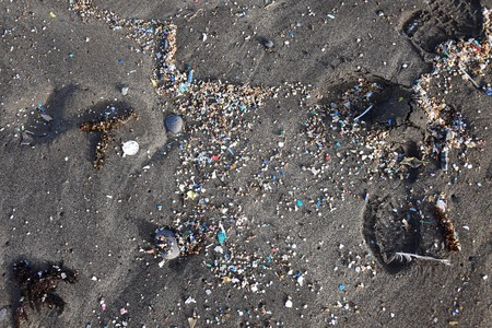 Small plastic parts and microplastics in the sand of Famara beach, Lanzarote, Spain. 免版税图像 - 122207174