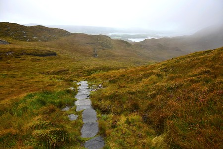 A narrow path made of stones leading through the Connemara National Park in Ireland. The weather is rainy and misty.