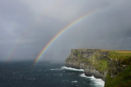 A rainbow over the Cliffs of Moher on the west coast of Ireland in County Clare. On the left is a second rainbow which is fading. Stock Photo