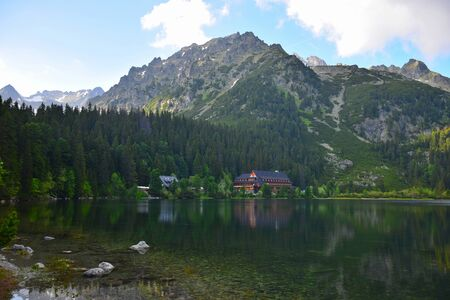The beautiful Popradske pleso with the mountain hotel Popradske pleso, surrounded by the Tatra mountains, in the evening sun. The scenery is reflected in the lake.