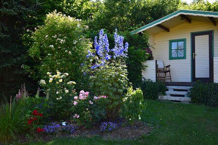 Ein Garten mit Gartenhaus, Stuhl und Blumen. Standard-Bild