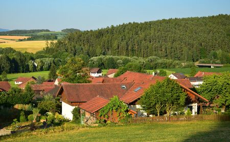 A small town in Bavaria in the summertime. A few houses, forest and fields in the background. Evening sun. Municipality of Traitsching, district of Cham, Upper Palatinate.