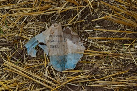 A blue and white piece of plastic foil in a field between soil an straw. 스톡 콘텐츠