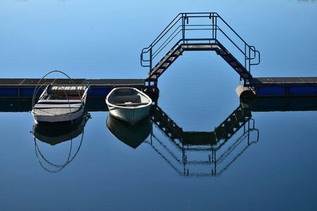 A lake, a boat bridge with a crossover and two boats. The scene is reflecting in the water.