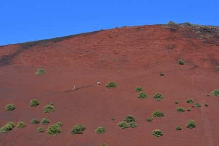 A couple walking up the red volcano Montana Colorada in Lanzarote, Spain. Stok Fotoğraf