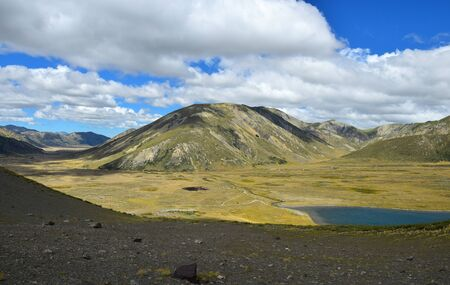 Beautiful landscape with lake Tennyson and mountains on the Molesworth station area, New Zealand, South Island. View from a mountain, in front a slope which is in the shade. 版權商用圖片