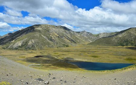 Beautiful landscape with lake Tennyson and mountains on the Molesworth station area, New Zealand, South Island. View from a mountain, in front a slope.