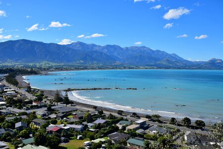 The town Kaikoura with its beach, ocean with turquoise water and mountains in the background. New Zealand, South Island.