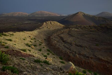 Beautiful volcanic landscape early in the morning in Lanzarote, Spain. The calima wind makes a surreal light. Far away in the back the small town Mancha Blanca.