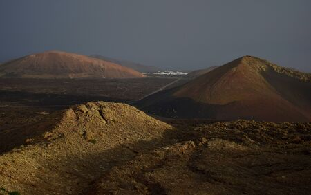 Beautiful volcanic landscape early in the morning in Lanzarote, Spain. The calima wind makes a surreal light. In the background the small town Mancha Blanca. 스톡 콘텐츠