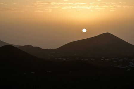 A sunrise in Lanzarote in February. Because the calima wind is blowing, there is lots of sand in the air. Canary Islands, Spain.