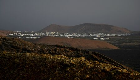 Beautiful volcanic landscape with a small town early in the morning in Lanzarote, Canary Islands, Spain. The calima wind makes a surreal light. 스톡 콘텐츠