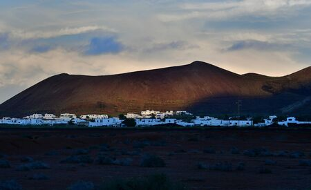 Beautiful volcanic landscape with a small town and white, traditional houses at sunset. Guatiza, Lanzarote, Canary Islands, Spain.