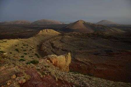 Beautiful volcanic landscape early in the morning in Lanzarote, Spain. The calima wind makes a surreal light. Far away in the background the small town Mancha Blanca. 스톡 콘텐츠