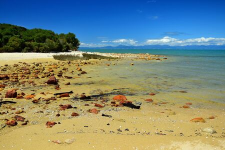 The Abel Tasman National Park. Golden sand and a blue sky. Red stones. New Zealand, South Island.