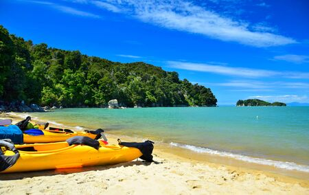 The Abel Tasman National Park. Colorful kayaks in the sand and a turquoise ocean. New Zealand, South Island.