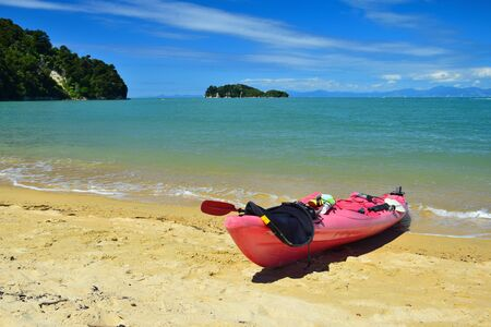 The Abel Tasman National Park. A red kayak in the sand and a turquoise ocean. New Zealand, South Island.