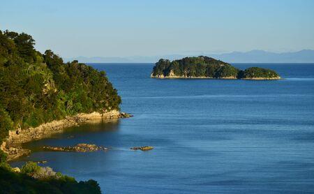 The Abel Tasman National Park. Coastline and an island in the evening sun. New Zealand, South Island.