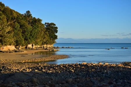 The Abel Tasman National Park. Coastline, a beach with sand and stones in the evening sun. New Zealand, South Island.