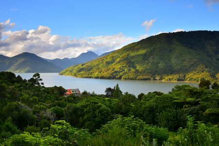 A house with a red roof in the Marlborough Sounds, Mahakipawa arm. Evening sun. New Zealand, South Island.