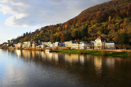 Heidelberg. Houses along river Neckar in autumn with the mountain Heiligenberg in the background.
