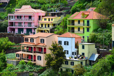 Colorful houses in green, pink, orange, blue and yellow. The small town Fontes at Madeira, Portugal. Image taken from public ground.