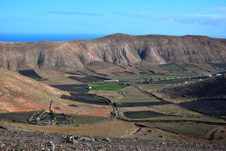 View to a valley with fields for agriculture. In the background the mountain range Los Ajaches. Near Femés. Lanzarote, Spain.