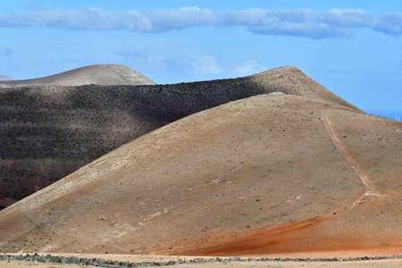 Beautiful volcanic landscape between Yaiza and Femes. Lanzarote, Canary Islands, Spain. A blue sky with some clouds.