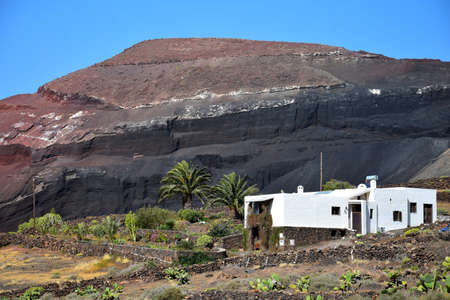 Beautiful volcanic landscape with a white house in front. Lanzarote, Canary Islands, Spain. Caldera de Masion near Femés. Image taken from public ground.