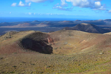 Top view of a crater. View from the mountain Atalaya de Femes near Femés. Lanzarote, Canary Islands, Spain. Timanfaya National park and Volcano Nature Park in the background.