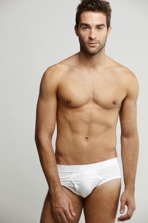 torso only: Portrait of mid adult man in briefs, studio shot