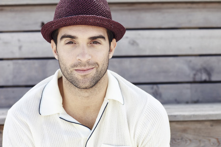 Portrait of mid adult man in red trilby, smiling photo
