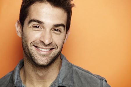 오렌지 배경에 웃는 중반 성인 남자의 초상화 스톡 콘텐츠