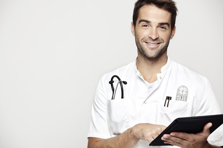 Portrait of mid adult doctor holding tablet against grey background photo