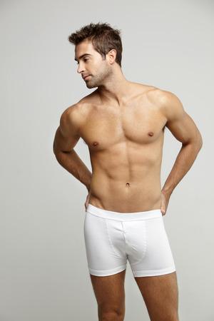 man in underwear: Mid adult man in underpants looking away, studio shotv