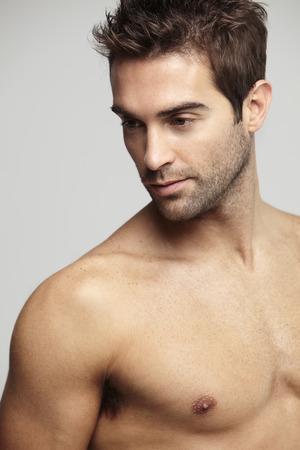 Shirtless mid adult man looking away, studio