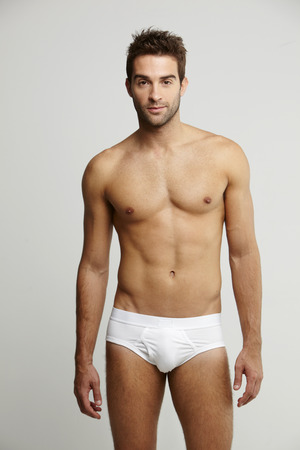 one mid adult man only: Portrait of mid adult man in briefs, studio shot